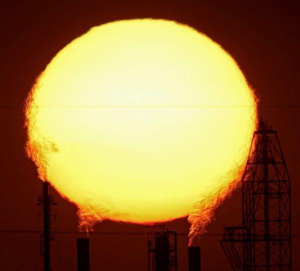 O sol entre as chaminés das fábricas